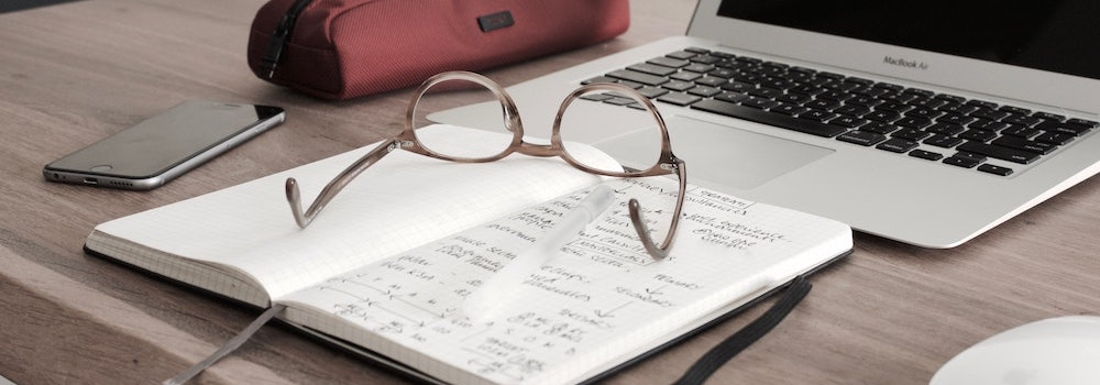 Desktop with note pad, laptop and glasses